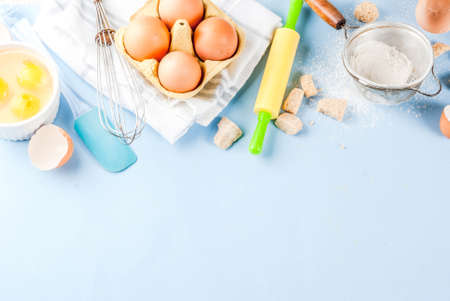 Ingredients and utensils for cooking baking egg, flour, sugar, whisk, rolling pin, on blue background, copy space top view