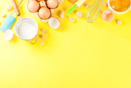 Ingredients and utensils for cooking baking egg, flour, sugar, whisk, rolling pin, on bright yellow background, copy space top view Stock Photo