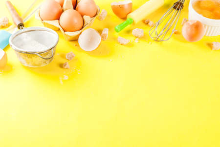 Ingredients and utensils for cooking baking egg, flour, sugar, whisk, rolling pin, on bright yellow background, copy space Stock Photo