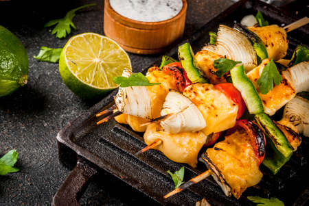 Vegan diet food, Grilled cheese and vegetables kebab, indian style Paneer Tikka, with white sauce and lime, on dark concrete background, copy space Stock Photo