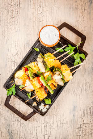 Vegan diet food, Grilled cheese and vegetables kebab, indian style Paneer Tikka, with white sauce and lime, on light concrete background, copy space top view