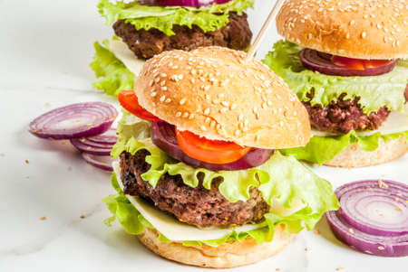 Fast food. Unhealthy food. Delicious Fresh Tasty Burgers with Beef Cutlet, fresh Vegetables and Cheese on white background. Copy space