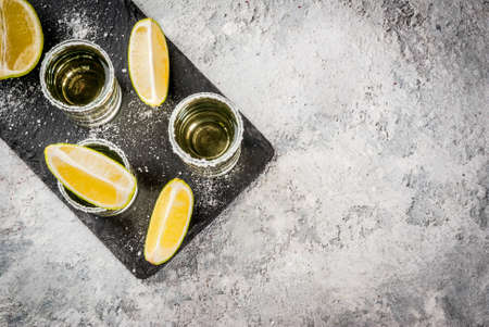 Tequila shots with lime and sea salt on grey stone table, copy space top view
