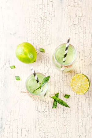 Healthy exotic detox drink, aloe vera or cactus juice with lime, on light concrete background copy space