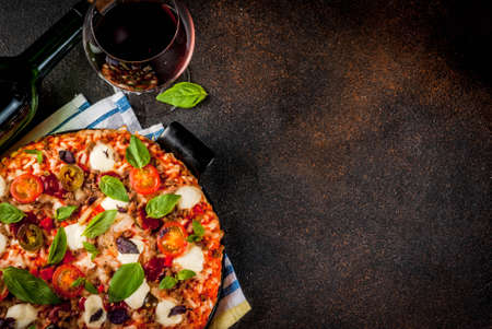Pizza and red wine on dark background top view copy space