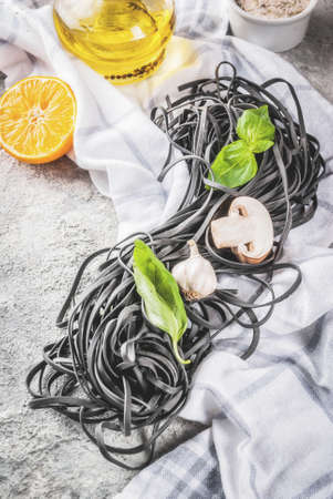 Raw uncooked black cuttlefish ink spaghetti pasta with ingredients for cooking dinner, on grey stone table top view Stockfoto