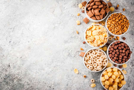 Set of various breakfast cereal corn flakes, puffs, pops, grey stone table copy space top view Фото со стока