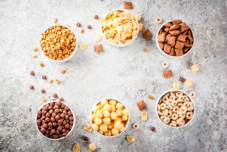 Set of various breakfast cereal corn flakes, puffs, pops, grey stone table copy space top view frame Stock Photo