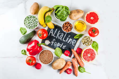 Healthy food background, trendy Alkaline diet products - fruits, vegetables, cereals, nuts. oils, white marble background top view copy space