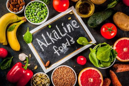 Healthy food background, trendy Alkaline diet products - fruits, vegetables, cereals, nuts. oils, dark blue concrete background above Stock Photo