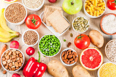 Diet food background concept, healthy carbohydrates (carbs) products - fruits, vegetables, cereals, nuts, beans, light concrete background above