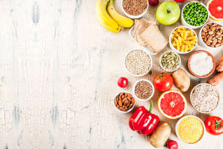Diet food background concept, healthy carbohydrates (carbs) products - fruits, vegetables, cereals, nuts, beans, light concrete background above copy space