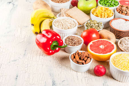 Diet food background concept, healthy carbohydrates (carbs) products - fruits, vegetables, cereals, nuts, beans, light concrete background copy space Stock Photo