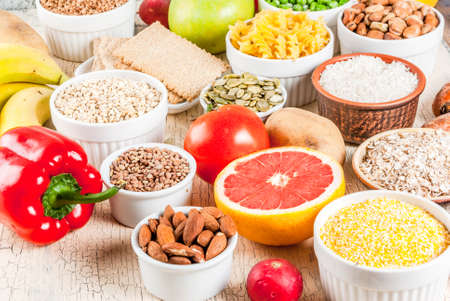 Diet food background concept, healthy carbohydrates (carbs) products - fruits, vegetables, cereals, nuts, beans, light concrete background Stock Photo