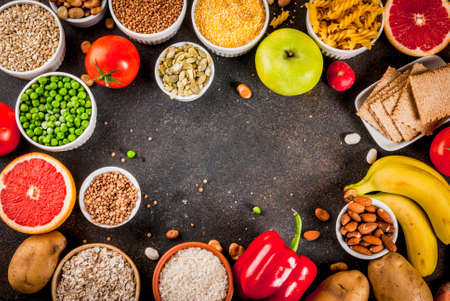Diet food background concept, healthy carbohydrates (carbs) products - fruits, vegetables, cereals, nuts, beans, dark blue concrete background copy space frame above