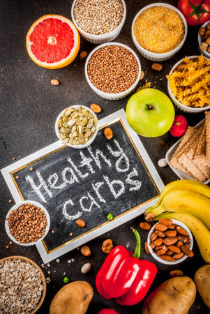 Diet food background concept, healthy carbohydrates (carbs) products - fruits, vegetables, cereals, nuts, beans, dark blue concrete background top view copy space Stock Photo