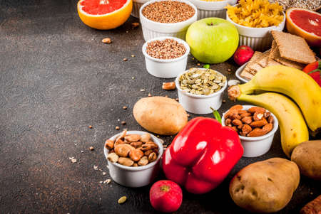 Diet food background concept, healthy carbohydrates (carbs) products - fruits, vegetables, cereals, nuts, beans, dark blue concrete background copy space