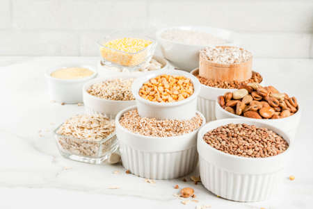 Selection various types cereal grains groats  in different bowl on white marble background, copy space