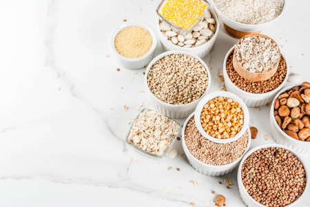 Selection various types cereal grains groats  in different bowl on white marble background, copy space top view