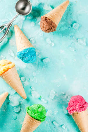 Selection of various bright multicolored ice-cream in ice cream cones - chocolate vanilla blueberry strawberry pistachio orange, on light blue sunny background, copy space top view