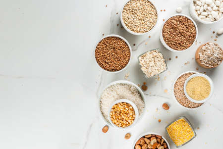 Selection various types cereal grains groats  in different bowl on white marble background, copy space above Stock Photo