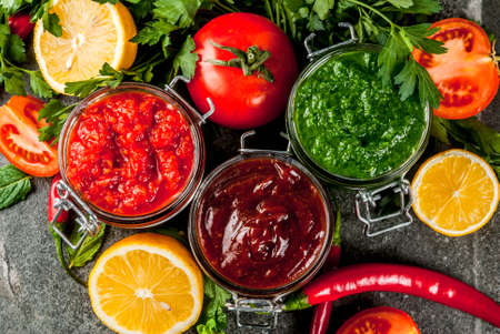 Indian traditional food, Set of three chutney for Chaat and Sev Puri - sweet date-tamarind, cilantro-mint green and red chilli garlic, On dark stone background, close top view Stock Photo
