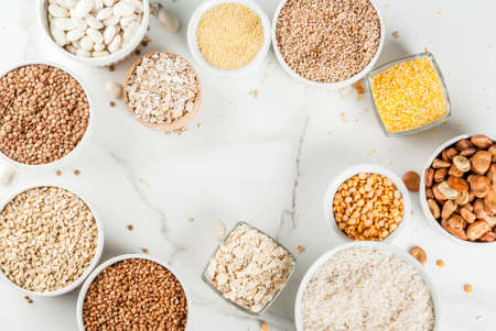 Selection various types cereal grains groats  in different bowl on white marble background, above frame copy space