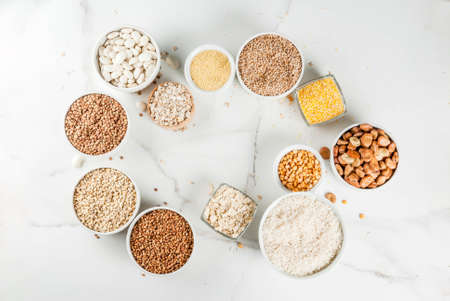 Selection various types cereal grains groats  in different bowl on white marble background, above frame space for text