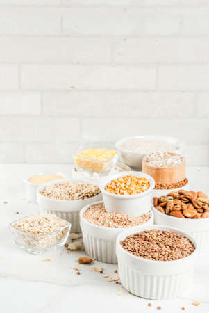 Selection various types cereal grains groats  in different bowl on white marble background,  space for text