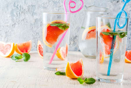 Summer refreshment detox water drink with Pink grapefruit and fresh mint, spa fruit water, lemonade or jin tonic cocktail, light concrete background copy space 写真素材 - 99848122