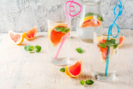 Summer refreshment detox water drink with Pink grapefruit and fresh mint, spa fruit water, lemonade or jin tonic cocktail, light concrete background copy space 写真素材 - 99848125