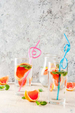 Summer refreshment detox water drink with Pink grapefruit and fresh mint, spa fruit water, lemonade or jin tonic cocktail, light concrete background copy space 写真素材 - 99848128