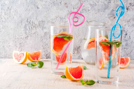 Summer refreshment detox water drink with Pink grapefruit and fresh mint, spa fruit water, lemonade or jin tonic cocktail, light concrete background copy space