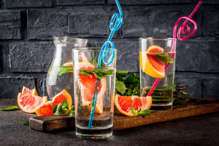 Summer refreshment detox water drink with Pink grapefruit and fresh mint, spa fruit water, lemonade or jin tonic cocktail, dark background copy space