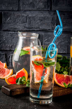 Summer resreshment detox water drink with Pink grapefruit and fresh mint, spa fruit water, lemonade or jin tonic cocktail, dark background copy space