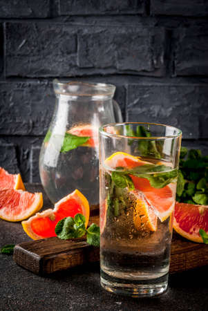 Summer refreshment detox water drink with Pink grapefruit and fresh mint, spa fruit water, lemonade or jin tonic cocktail, dark background copy space 写真素材 - 99848137