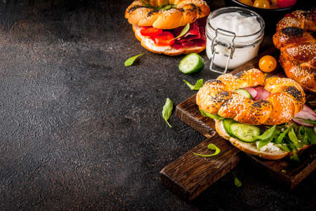 Variety of homemade bagels sandwiches with sesame and poppy seeds, cream cheese,  ham, radish, arugula, cherry tomatoes, cucumbers, with ingredients on dark concrete background copy space Zdjęcie Seryjne