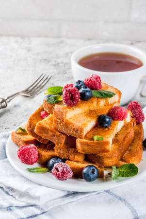 Healthy summer breakfast, baked french toasted bread sticks with fresh berry and honey, morning light grey stone background copy space 스톡 콘텐츠