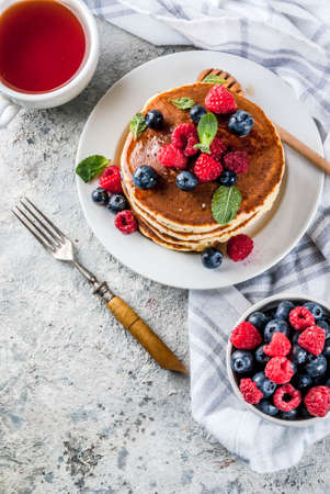 Healthy summer breakfast,homemade classic american pancakes with fresh berry and honey, morning light grey stone background copy space above