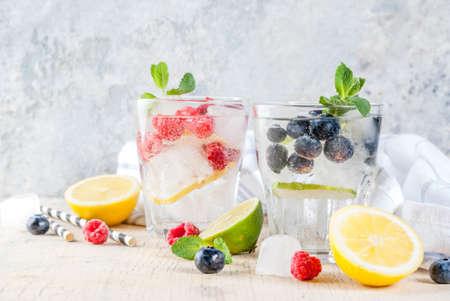 Divers cocktails de limonade ou de mojito aux baies, eau infusée fraîche de citron vert citron vert framboise myrtille, boissons détox saines d'été, espace de copie de fond clair Banque d'images