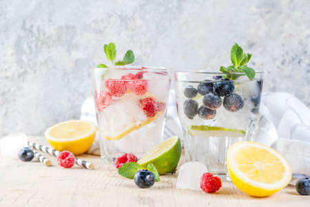 Various berry lemonade or mojito cocktails, fresh iced lemon lime raspberry blueberry infused water, summer healthy detox drinks light background copy space Foto de archivo