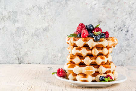 Belgian waffles with raspberries, blueberries and syrup, homemade healthy breakfast, light concrete background copy space Imagens - 100021099