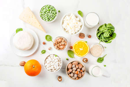 Healthy food concept. Set of food rich in calcium - dairy and vegan Ca products, white marble background top view