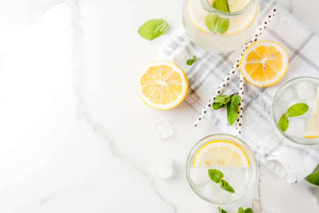 Summer refreshing drinks, mojito or lemonade with fresh mint, slices of lemon, ice, on a light background. copy space top view