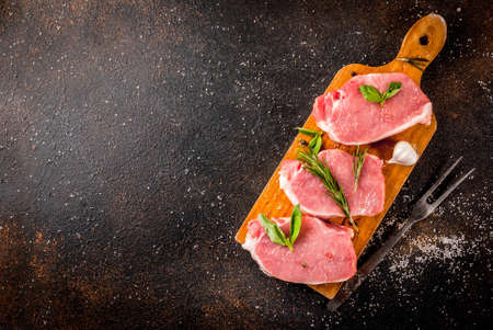 Raw meat, pork steaks with spices, herbs, olive oil, dark background top view, copy space Stock Photo