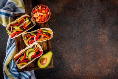 Homemade Mexican pork tacos with vegetables and salsa, on dark rusty table top view Stockfoto