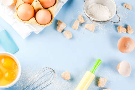 Ingredients and utensils for cooking baking egg, flour, sugar, whisk, rolling pin, on blue background, top view copy space