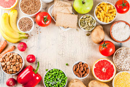 Diet food background concept, healthy carbohydrates (carbs) products - fruits, vegetables, cereals, nuts, beans, light concrete background  copy space  frame above
