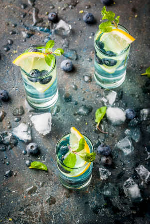 Summer refreshment drinks, Blueberry Lemonade or mojito cocktail with lemon, fresh blueberries and mint, sdark blue stone background copy space top view