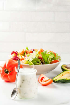 Classic homemade ranch  salad dressing, with fresh vegetables on white marble table, copy space